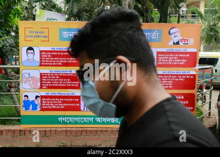 Dhaka, Bangladesh. 18th June, 2020. A man passes a poster carrying messages on symptoms and awareness of coronavirus disease inside hospital premises in Dhaka, Bangladesh, June 18, 2020. Credit: Suvra Kanti Das/ZUMA Wire/Alamy Live News - Stock Photo