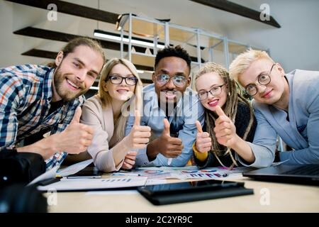 Group of skilled five multiethnic designers, architects, freelancers, working together on project, leaning on the table, smiling to camera and showing - Stock Photo