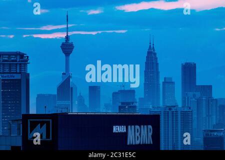evening sunset city scape with tower blocks personas towers and menara Kuala Lumpur communications tower Malaysia - Stock Photo
