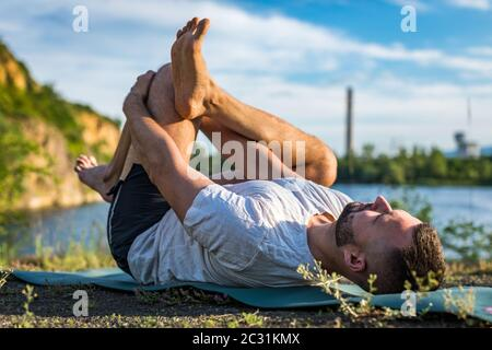 Young man doing yoga in morning park. Bearded man relax and streching in nature. International Day of Yoga