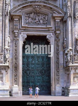 Bronze central door on facade of Duomo di Milano (Milan Cathedral), Piazza del Duomo, Milano (Milan), Lombardy Region, Italy - Stock Photo