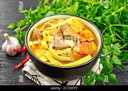 Central Asian national dish Lagman of meat, noodles and vegetables in bowl on a napkin, garlic, parsley on wooden board background - Stock Photo