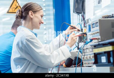 Team of engineers, woman and man, testing and measuring an electronic product in the lab together - Stock Photo