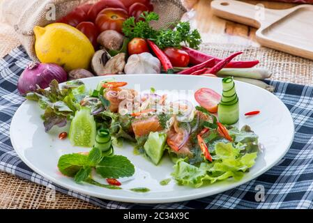 Fresh Salmon Salad with vegetables,healthy salad with mixed lettuce leaves on a white dish on a old rustic table, easy recipe, top view Thai style