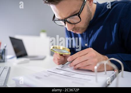 Close-up Of A Businessperson's Hand Looking At Receipts Through Magnifying Glass At Workplace Stock Photo