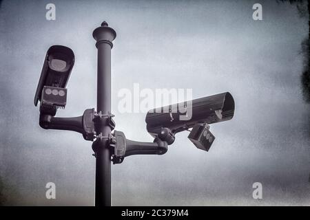Two CCTV security cameras mounted on a pole in street. - Stock Photo