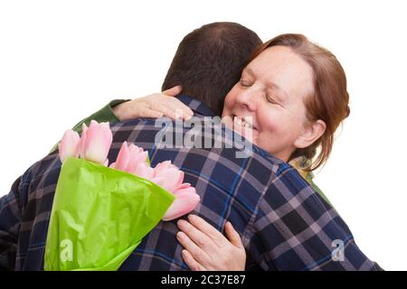 Man with bouquet of pink tulips hidden behind his back hugging elderly woman, isolated on white background. Mothers day, Valenti