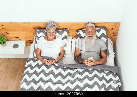 Happy senior couple using mobile smartphones below blankets in bed - Mature people having funny bed time watching on new media trends - Stock Photo