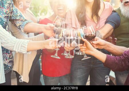 Happy family toasting with red wine glasses at dinner outdoor - People having fun cheering and drinking while dining together - Stock Photo