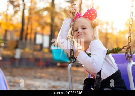 Little cute adorable caucasian blond school girl enjoy having fun sitting and riding old chain swing carousel at city theme amusement park. Happy - Stock Photo