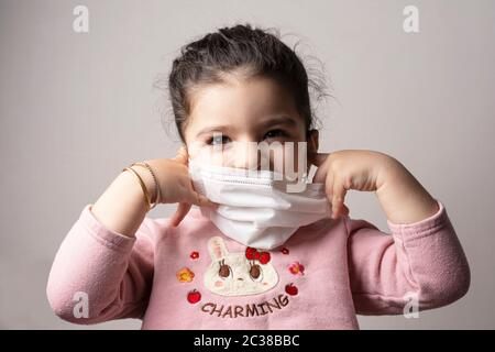 Little girl removing hospital mask from her face, coronavirus outbreak and air pollution concept - Stock Photo