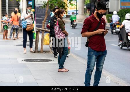 Passengers with face mask social distancing at bus stop during Covid 19 pandemic, Bangkok, Thailand - Stock Photo