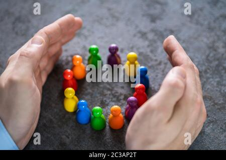 Close-up Of A Person's Hand Protecting Multicolored Pawns Forming Circle Over White Desk - Stock Photo