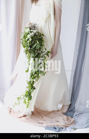 Bride in delicate gown with bouquet of small white flowers