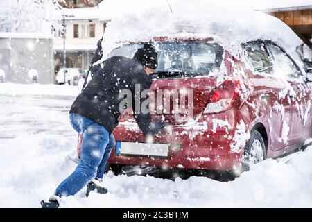 Man Pushing A Car Stuck In The Snow After Heavy Snowfall - Stock Photo