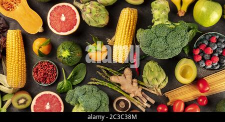 Vegan food panorama, overhead shot of fresh fruits, vegetables, pasta, legumes, and mushrooms, a flat lay - Stock Photo