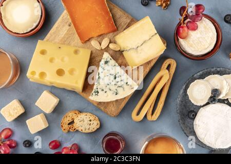 Various cheeses assortment with wine and fruit. Blue cheese, Brie, Dutch cheese and others, shot from above - Stock Photo