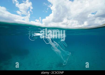 Plastic waste pollution in sea since coronavirus COVID-19 pandemic, face mask with gloves underwater and sky with cloud, split view over under water