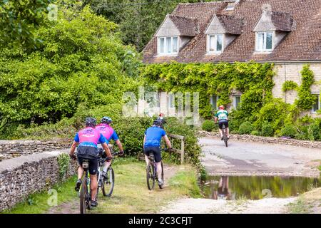 Cyclists passing cottages beside the ford in the Cotswold village of Duntisbourne Rouse, Gloucestershire UK - Stock Photo