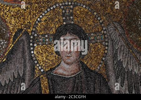 Jesus Christ, flanked by the feathered wings of archangels against a background of golden tesserae, is depicted as young, beardless, and with a cruciform halo ringed and studded by inlaid discs of mother of pearl in this close detail view of the Christ the Redeemer mosaic filling the apse dome of the 6th century AD Basilica di San Vitale at Ravenna, Emilia-Romagna, Italy.   The mosaic was created a few years after Byzantium captured Ravenna in 540 AD.  The city is now Western Europe's greatest centre for the study of Byzantine art and architecture and is a UNESCO World Heritage site. - Stock Photo