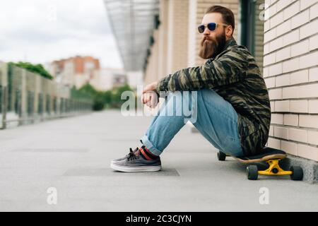 Handsome young man sitting on the longboard on the street in the city. Urban skateboarding concept. - Stock Photo