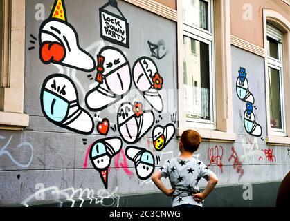 Dortmund, Germany, June 19th, 2020: Mask worms. Since the outbreak of the corona crisis in March 2020, small corona virus graffiti with a mouth mask created by an unknown sprayer can be seen on many house walls in Dortmund.   ---   Dortmund, 19.06.2020: Maskenwürmchen. Seit Ausbruch der Corona-Krise im März 2020 sind kleine Coronaviren-Graffitis mit Mundschutz eines unbekannten Sprayers an vielen Hauswänden in Dortmund zu sehen.