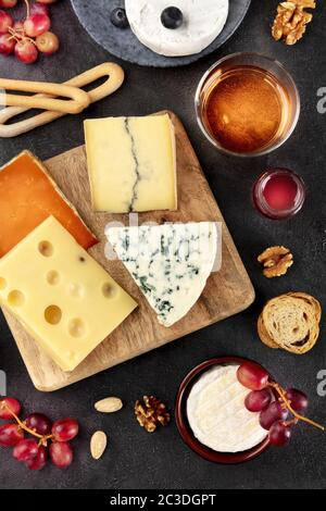 Cheese platter. Blue cheese, Brie, Emmental and others with wine, shot from the top on a black background - Stock Photo
