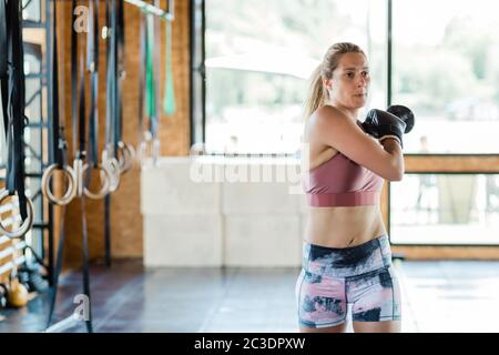 Young sporty woman warming up for boxing exercise