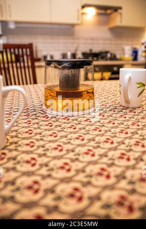 Glass custard with tea and cups on the kitchen table in the background of the kitchen. Place for text. The concept of happy family life - Stock Photo