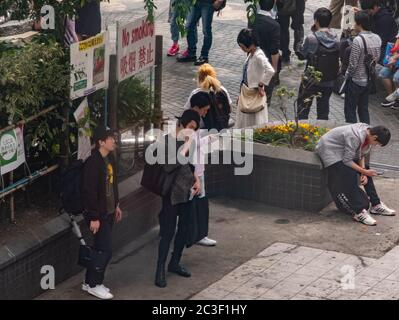 Smokers smoking at a designated area in Shibuya, Tokyo, Japan - Stock Photo