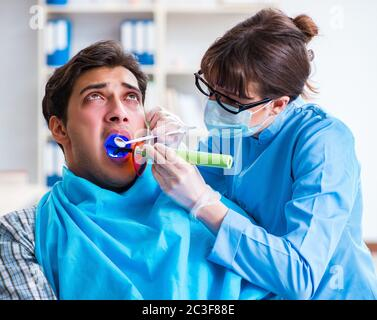 Patient afraid of dentist during doctor visit - Stock Photo