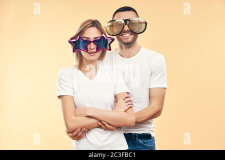 Young happy couple in funny party glasses on beige background - Stock Photo