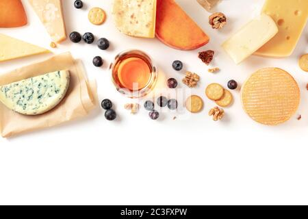 Cheese and wine tasting and pairing flat lay on a white background with copy space. Many different cheeses, shot from the top - Stock Photo