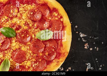 Pepperoni pizza close-up on a black background, shot from the top with a place for text - Stock Photo