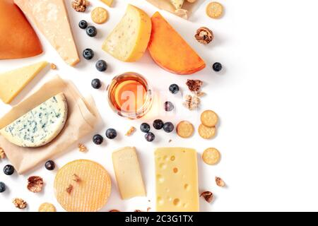 Cheese and wine tasting and pairing flat lay on a white background with a place for text. Many different cheeses, shot from abov - Stock Photo