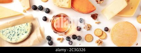 Cheese and wine tasting and pairing flat lay panorama on a white background with a place for text. Many different cheeses, shot - Stock Photo