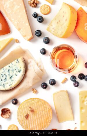Cheese and wine tasting and pairing flat lay on a white background. Many different cheeses, overhead shot - Stock Photo