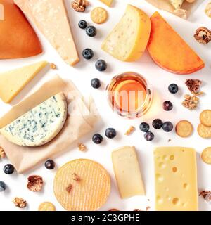 Cheese and wine tasting and pairing flat lay on a white background. Many different cheeses, overhead square shot - Stock Photo