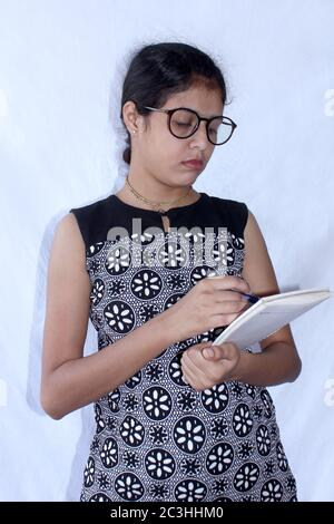 A young Asian woman standing and writes something in a notebook over on white background, selective focus. - Stock Photo