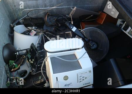 Waste Electrical and Electronic Equipment Directive collected in a waste container before being transported into a recycling facility. - Stock Photo