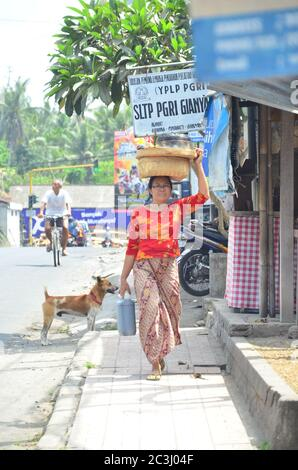Woman with a basket on her head on Ubud market in Bali, Indonesia. - Stock Photo