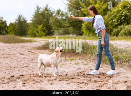 Woman giving a command to her obedient dog