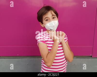 Child girl wearing a protection mask against coronavirus during Covid-19 pandemic - Stock Photo