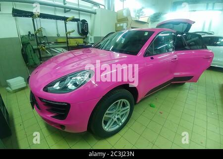 Moscow, Russia - May 09, 2019: Porsche Macan in service center, car wrapping, putting pink vinyl foil or film on car. - Stock Photo