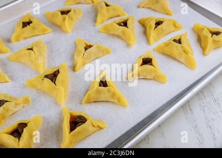 Raw hamentaschen cookies with chocolate chips on baking tray for Jewish holiday Purim. - Stock Photo