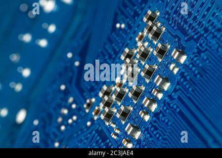 Macro photo of electrical paths on blue circuit board, visible resistors. - Stock Photo