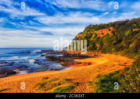 Calm secluded TUrimetta beach at low tide on Pacific ocean coast of Sydney in soft morning light.