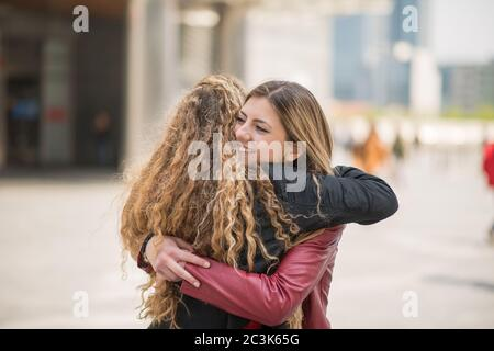 Female friends meeting in a city - Stock Photo