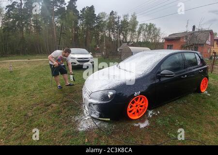 Kolomna, Russia - April 1, 2019: A man washes his car against the background of the forest. Tuned Volkswagen Golf 6 stands on the grass on the lawn. Black and white hatchbacks at the car wash - Stock Photo