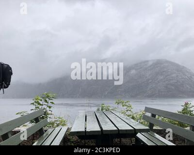 Two benches and a table in front of the mountain and the water under a clouded sky - Stock Photo